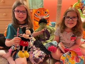 Two bespectacled girls smile for the camera holding their knitting projects surrounded by their stuffed toys